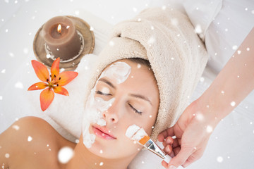 Attractive woman receiving treatment at spa center against snow falling © vectorfusionart