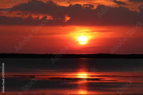 Plexiglas Bordeaux Vibrant and dramatic full sun sunset swirl red clouds cloudscape