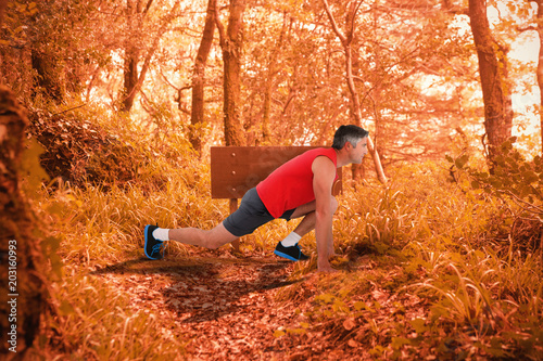 Fit man stretching his legs against tranquil autumn scene in forest - 203160993