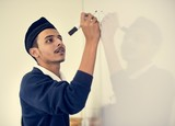 young muslim student writing on white board