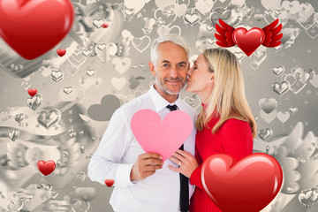Handsome man holding paper heart getting a kiss from wife against grey valentines heart pattern