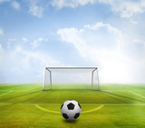 Black and white football against football pitch and goal under blue sky - 203171569