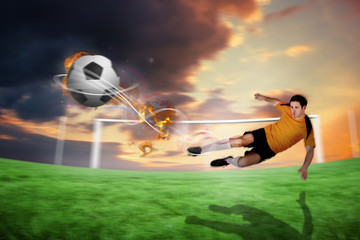 Football player in orange kicking against football pitch under cloudy orange sky