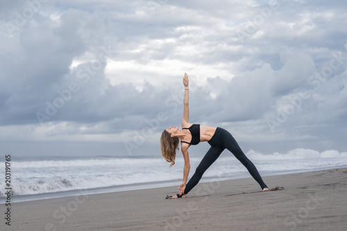Fototapeta beautiful young woman practicing yoga in Triangle pose (Trikonasana) on seashore