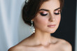 Close-up portrait of the bride with diamond earrings, wedding make-up and hairdo poses in a dark studio. Beautiful young brunette girl on black and white background. Concept of marriage, clear skin