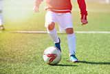 Foot of child football player and ball