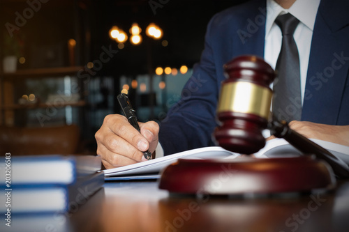 Foto Murales Close up lawyer businessman working or reading lawbook in office workplace for consultant lawyer concept.