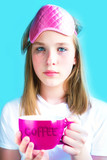 young teenage girl sleepy with matches in her eyes drinks coffee in the morning from a big cup with an inscription a COFFEE on a pink blue vanilla trend background with copy space pop art sty