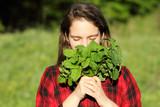 девушка в руках держит в руках лечебное растение мелиссу  - 203226790