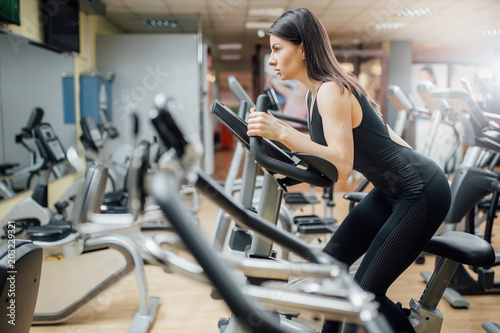 Wall mural Woman training on exercise bike in a spinning class in gym,