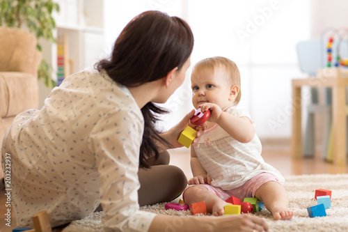 Cute baby girl playing with educational toys in nursery. Child having fun with colorful different toys at home. Nanny looks after kid toddler. © Oksana Kuzmina