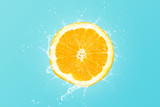 Fresh orange slice with water splash on blue background