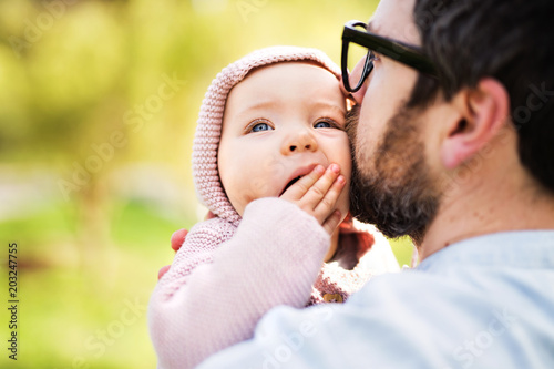 A father with his toddler daughter outside in spring nature.