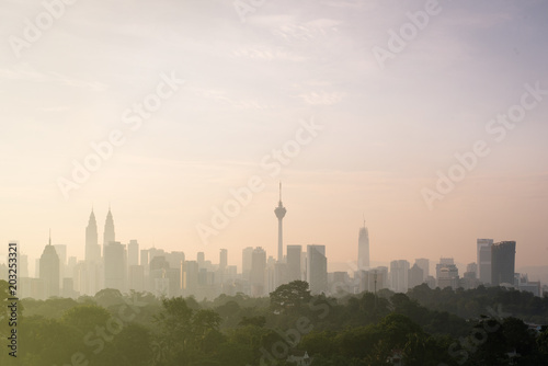 beautiful view of Kuala Lumpur city skyline in the early morning with haze or fog and building is semi silhouette. tourism and cityscape concept