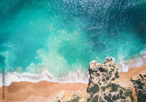 Aerial view of sandy beach and ocean with beautiful clear turquoise water.