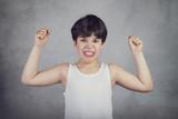 niño fuerte que enseña sus músculos sobre fondo gris - 203265973