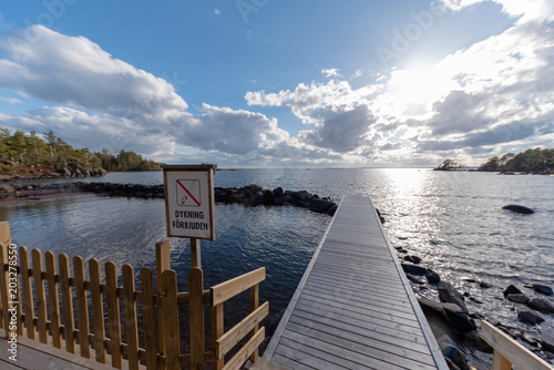 Fotobehang Pier wooden jetty with a sign diving forbidden in swedish
