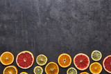 Flat lay of citrus fruits pattern of lemon, orange and grapefruit on black stone background. Copy space above. Top view.