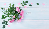 Top view of pink roses and bridal rings for wedding on background of shabby wooden planks