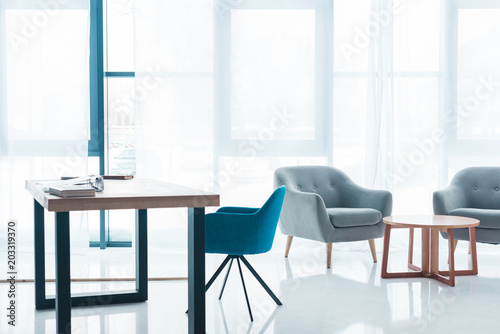cozy modern office interior intended wooden table and empty cozy armchairs in modern office interior
