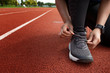 Runner tying shoes on run tracks lanes in stadium  ready for race competition