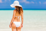 Back of young woman in bikini standing on the beach - 203334709