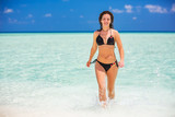 Attractive young woman enjoys Maldivian beach running in the ocean water - 203334720