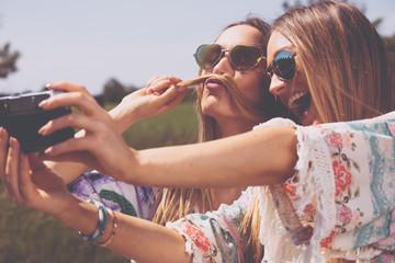 zwillings schwestern machen selfies mit einer retro kamera