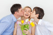 Man and son gives a bouquet of flowers to woman