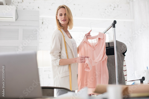 Better choice. Low angle of appealing female couturier looking at screen while holding garment