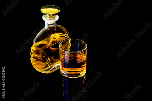 Decanter and a glass of whiskey on a black background