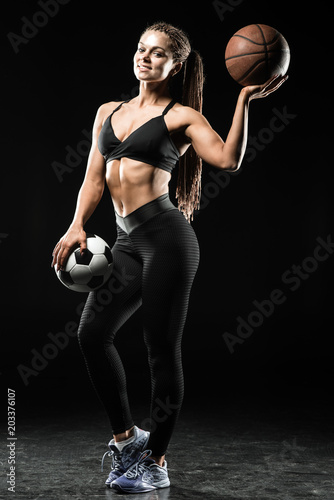 Fotobehang Basketbal Beautiful girl holding soccer and basketball balls isolated on black background