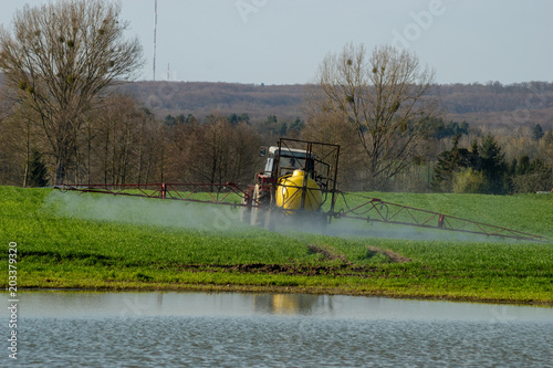 Aluminium Trekker Farmer on tractor spraying green wheat field