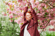 canvas print picture - Beautiful young woman with red hair having fun standing in cherry blossom tree, springtime garden mood