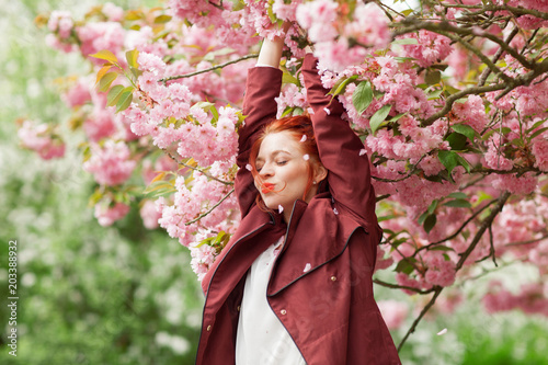 canvas print picture Beautiful young woman with red hair having fun standing in cherry blossom tree, springtime garden mood