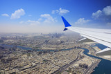 Dubai cityscape, aerial view from airplane window in a sunny day with clear blue sky