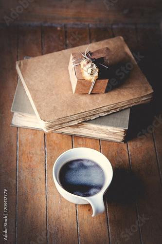 biala-filizanka-z-kawa-i-ksiazkami-na-drewnianym-stole-wysoki