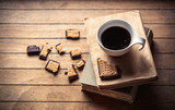 White cup with coffee and books, cookie on wooden table. High angle view