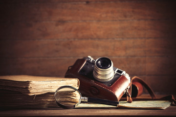 little magnifier and book with camera on a table. Image in old color style