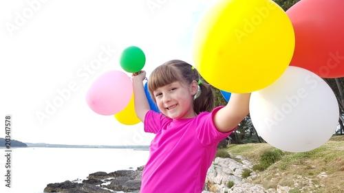 Bambina che gioca con i palloncini colorati al tramonto