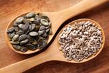 Semi di girasole e semi di zucca nei cucchiai di legno. - 203418913