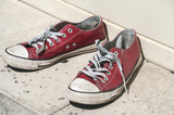 Abandoned heavy used old grunge weathered red sport sneakers on street stone surface