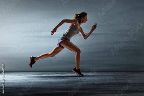Leinwanddruck Bild Läuferin vor grauer Wand