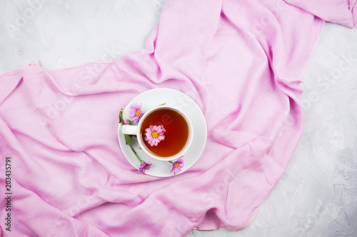 Foto Murales Cup of black tea with pink daisy flower inside on pink scarf on cement background, flatlay
