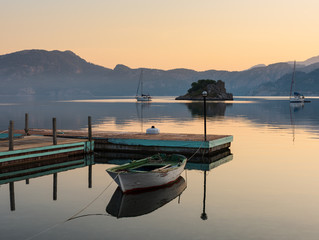 Small boats in the sunrise reflected in the mountains