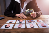 Businessperson Looking At Candidate's Photograph - 203475740