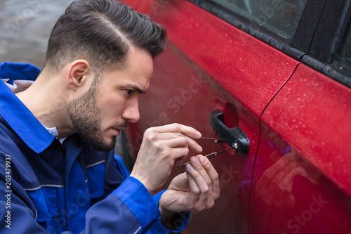 Wall mural Man Opening Car Door With Lockpicker