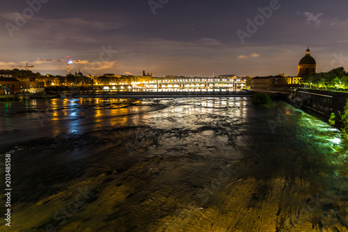 Night view of Toulouse, France, and the Garonne river, with the St Pierre bridge and the la Grave dome in the background.