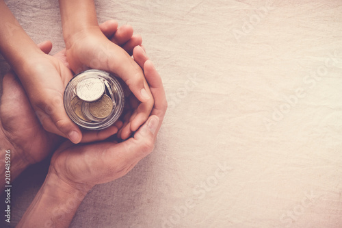 child and adult holding money jar, donation, saving concept