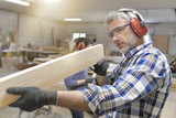 Wood worker cutting piece of wood with machine - 203493701